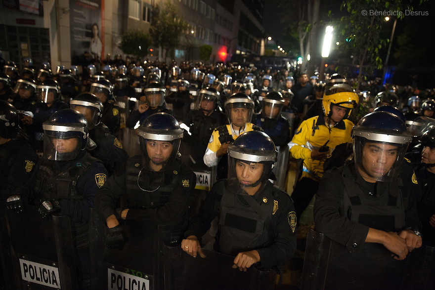 Riot policemen at the New Year's Eve protest for the disappearance of 43 Ayotzinapa's students, near Los Pinos presidential residence in Mexico City, Mexico on December 31, 2014. The relatives of the 43 missing students do not believe the official line that the young men are all dead. The 43 students went missing on Sept. 26 after confrontations in which police gunfire killed six people and wounded at least 25 in Iguala, in Guerrero state. Alexander Mora Venancio, one of the 43 Ayotzinapa's missing students, has been identified and confirmed dead by authorities. Many are demanding justice and that the search for the 42 missing students continue until there is concrete evidence to the contrary. Mexico – officially - lists more than 20 thousand people as having gone missing since the start of the country's drug war in 2006, and the search for the missing students has turned up other, unrelated mass graves. (Photo by Bénédicte Desrus)