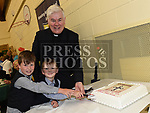 Canon Peter Murphy who was celebrating 40 years in the priesthood cuts his cake with his nephews James and Martin Murphy. Photo:Colin Bell/pressphotos.ie