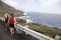 A couple of bicyclists (bicyclist) with bicycles (bicycle), take a break on the side of Kalanianaole Highway on the windward coast of Oahu