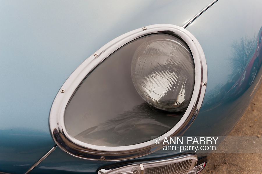 This headlight covered in glass is close up of 1967 E Type Jaguar 4.2 Series 1 at the 58th Annual Easter Sunday Vintage Car Parade and Show sponsored by the Garden City Chamber of Commerce. Hundreds of authentic old motorcars, 1898-1988, including antiques, classic, and special interest participated in the parade.