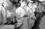"Masked Hamas militants, dressed as ""martyrs"" for an honor guard while wearing mock ups of a suicide-bomber's ""belt of explosives"" pray during the funeral of their slain leader Abdel Rahman Hamad October 14, 2001 in the West Bank town of Qalqilya, hours after the Islamic activist was gunned down by Israeli special forces. Israeli military sources said that Hamad was responsible for two suicide bombings earlier this year which killed 25 young people, mostly at the Dolphinarium Discotheque in June. The targeted killing of one of Israel's ""most wanted"" has dealt a blow to America's attempts to get Israel and the Palestinians to end their year-long violent conflict which threatens Middle East support for the ""War on terror"" launched after the September 11 attacks on the United States. Photo by Quique Kierszenbaum"