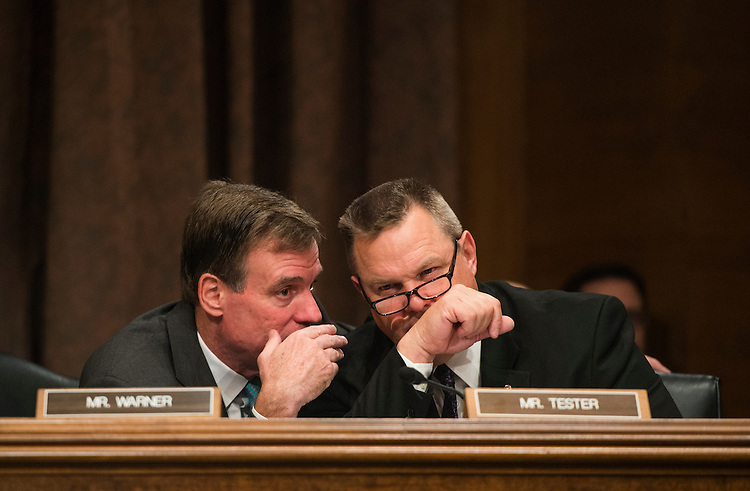 "UNITED STATES - OCTOBER 10: From left, Sen. Mark Warner, D-Va., and Sen. Jon Tester, D-Mont., talk during the Senate Banking, Housing and Urban Affairs Committee hearing on ""Impact of a Default on Financial Stability and Economic Growth"" on Thursday, Oct. 10, 2013. (Photo By Bill Clark/CQ Roll Call)"