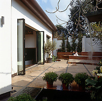 Large folding glass doors open from the dining room onto a walled garden with a water feature and terraced decking
