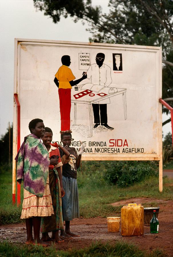 1994. Burundi. During the Rwandan Genocide, young women stand in front of a billboard illustrating an AIDS campaign. Besides the gravity of the conflict, Africa's most serious problem is AIDS. Burundi. Pendant le génocide au Rwanda, des jeunes femmes se tiennent devant une affiche de la campagne de lutte contre le sida. En dehors de la gravité du conflit, le principal problème en Afrique est le sida.