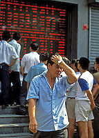 Businessmen check outdoor screens showing stock prices at the Shenzhen Stock Exchange, China.