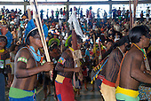Altamira, Brazil. Encontro Xingu protest meeting about the proposed Belo Monte hydroeletric dam and other dams on the Xingu river and its tributaries. Kayapo men dancing immediately after the incident with Paulo Fernando Vieira Souto Rezende, one with a piece of his shirt on his borduna war club.