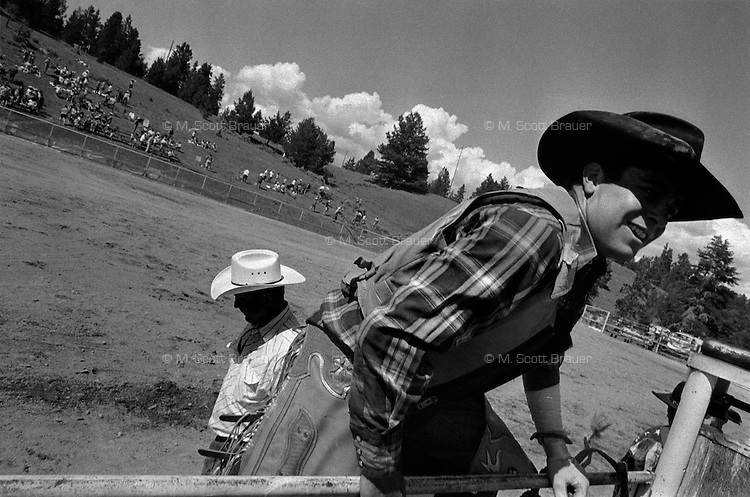 A cowboy climbs out of the arena while a rodeo judge walks past after the cowboy's run at the annual Lincoln Rodeo in Lincoln, MT in June 2006.  The Lincoln Rodeo is an open rodeo, which means competitors need not be a member of a professional rodeo association.