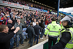 A police officer in riot gear watching as Crystal Palace supporters celebrating at Hillsborough at the final whistle of the crucial last-day relegation match against Sheffield Wednesday. The match ended in a 2-2 draw which meant Wednesday were relegated to League 1. Crystal Palace remained in the Championship despite having been deducted 10 points for entering administration during the season.