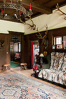Trophies, antlers stools and a fur covered sofa deliver an authentic hunting lodge atmosphere