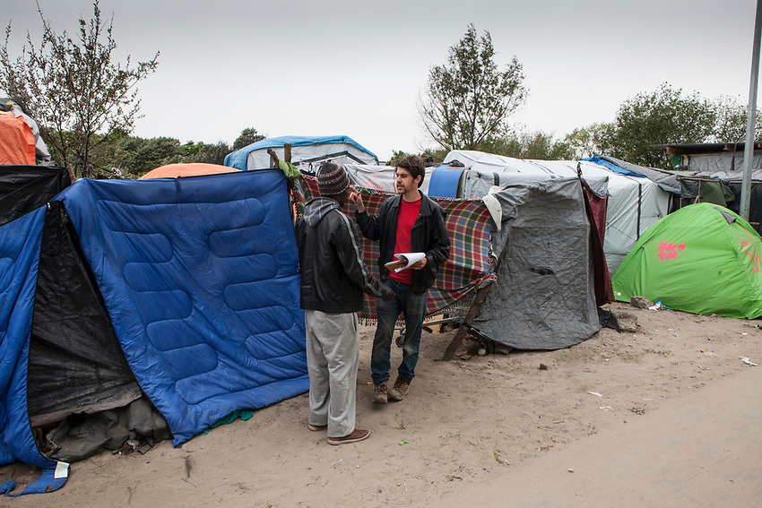 """Jack Steadman, who is taking a census of the camp talks to a refugee.  Photographed in """"The Jungle"""" refugee camp in Calais France. Help Refugees UK has grown out of #helpcalais, a social media campaign started by Lliana Bird (Radio X DJ), Dawn O'Porter (Writer and Presenter), Josie Naughton and Heydon Prowse (The Revolution will be Televised) to raise a few funds and collect goods to take to Calais to help in some small way. The public response to the campaign was huge, and we were quickly able to provide aid in Calais and far beyond. Dani Lawrence' involvement begin when she filled a car with supplies and donations and drove to Calais."""