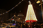Palestinians watch the lighting of a Christmas tree outside the Church in West Bank town of Nablus  Monday, Dec. 19, 2011. Christian worshipers began their spiritual preparations ahead of Christmas Eve and tourists from all over the world are expected to flock to Jesus' traditional birthplace to celebrate the Christmas holiday in Bethlehem on 24 December. ..Palestinian Christians celebrate Christmas near a church in the West Bank town of Nablus. Monday , Dec. 19, 2011 . Photo by Wagdi Eshtayah.