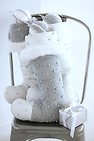 Three grey and silver Christmas stockings packed full of decorations and gifts on a metal chair