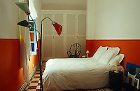 This simple bedroom has a tiled floor and walls painted up to an imaginary dado rail in orange