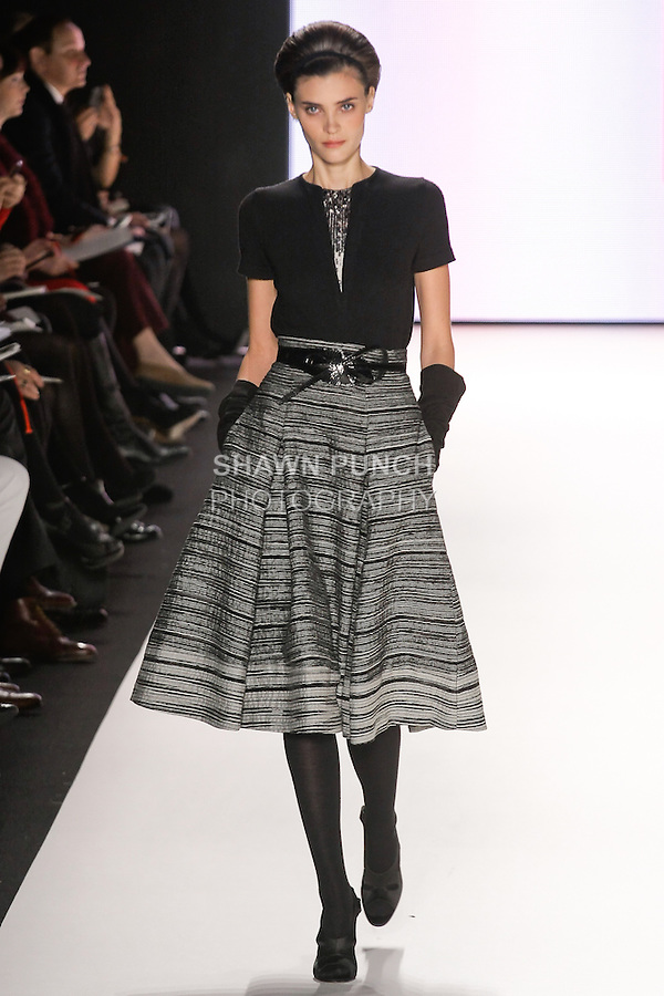 Alison Nix walks runway in a black and canvas embroidered knit top, canvas and black silk melange organza skirt, black suede gloves, black snake skin wrap belt, from the Carolina Herrera Fall 2012 collection, during Mercedes-Benz Fashion Week Fall 2012 in New York.