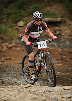 NWA Democrat-Gazette/ANDY SHUPE<br /> Rickie Rainwater of Fayetteville rides across Lee Creek Saturday, Sept. 19, 2015, during the Northwest Arkansas Mountain Bike Championships at Devil's Den State park.