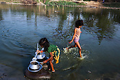 Young girls collect the utensils after washing them in the pond in Saptari, Nepal.