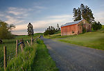 Washington, Eastern, Colfax, Steptoe. A faded red barn with stone foundation in the evening light of spring on the Palouse.