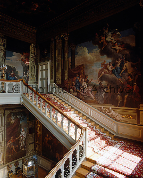 The Grand Staircase at Petworth House is decorated with murals by Louis Laguerre and the balustrade is by Sir Charles Barry