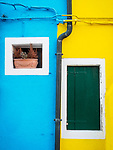 But and yellow walls and windows. The colorful village of Burano, Italy.