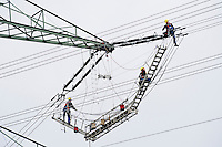 GERMANY, installation of new electric power lines to transport wind energy from North to South, worker on lattice steel tower of electric grid / DEUTSCHLAN , Ausbau der Stromnetze, Aufbau und Verkabelung einer neuen Hochspannungsleitung entlang der A24 zwischen Schleswig Holstein und Mecklenburg Vorpommern - Netzwerke, Vernetzung, network