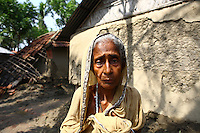 An elderly woman stands beside her home damaged by Cyclone Aila. Thousands of people were displaced in Shyamnagar Upazila, Satkhira district after Cyclone Aila struck Bangladesh on 25/05/2009, triggering tidal surges and floods..