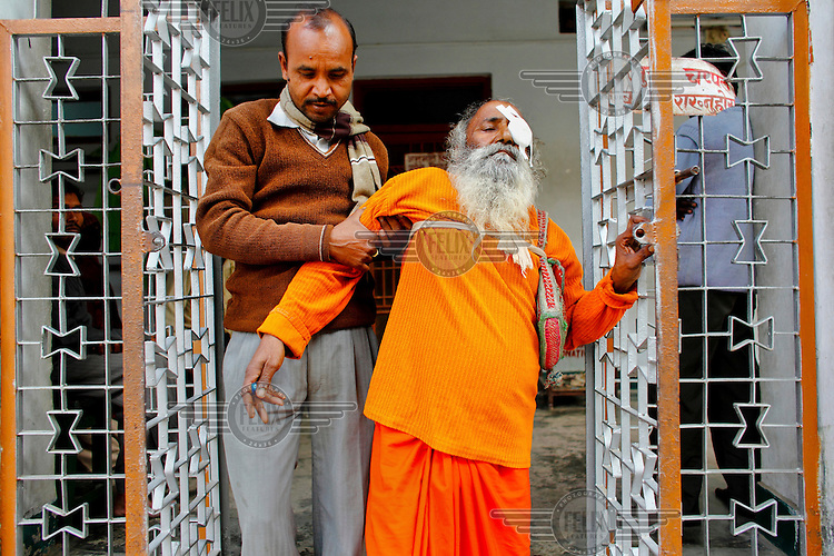 60 year old Ram Chandra is helped after his operation to remove his cataract at the GETA eye hospital.