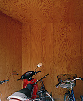 A red scooter and bicycles in the wooden shed