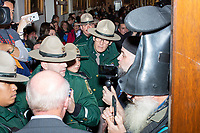Satirical presidential candidate Vermin Supreme (boot on head) and supporter/possible candidate Rod Webber try to gain access to the Secretary of State's office before Democratic presidential candidate and Massachusetts senator Elizabeth Warren arrives to officially file paperwork to get on the primary ballot at the NH State House in Concord, New Hampshire, on Wed., November 13, 2019. State Police eventually got the pair to stay outside the room. Vermin Supreme has been on the ballot for about two decades, though this year he is running for the Libertarian ticket and doesn't need to go through the Secretary of State's filing process.