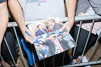 """A man holds a photo of President Barack Obama and entrepreneur and Democratic presidential candidate Andrew Yang hoping to get an autograph from the candidate after he spoke to a large crowd in Cambridge Common near Harvard Square in Cambridge, Massachusetts, on Mon., September 16, 2019. Yang's unlikely presidential bid is centered on his idea for a """"Freedom dividend,"""" which would give USD$1000 per month to every adult in the United States. After appearing in three Democratic party debates, Yang has risen in polls from longshot candidate to within the top 10."""