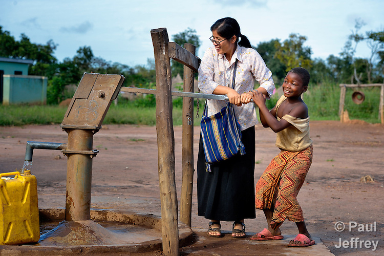 Sister Rosa Le Thi Bong, a Vietnamese member of Sisters of Our Lady of the Missions, helps a girl pump water from a well in the Makpandu refugee camp, a ramshackle collection of huts with mud walls and thatched roofs spread through a remote section of forest 40 kilometers from Yambio, the capital of Western Equatoria State in the newly independent South Sudan. More than 3,000 people live in the camp, having fled the Democratic Republic of the Congo in 2008 when the Lord's Resistance Army started a murderous rampage through the area. In recent months the Congolese have been experiencing harassment and insults from the local population. Religious workers say the refugees want to go home to the Congo, but not until Joseph Kony and the LRA are removed. Sister Rosa works in the camp as a member of Solidarity with South Sudan, a pastoral and teaching presence of Catholic priests, sisters and brothers from around the world.