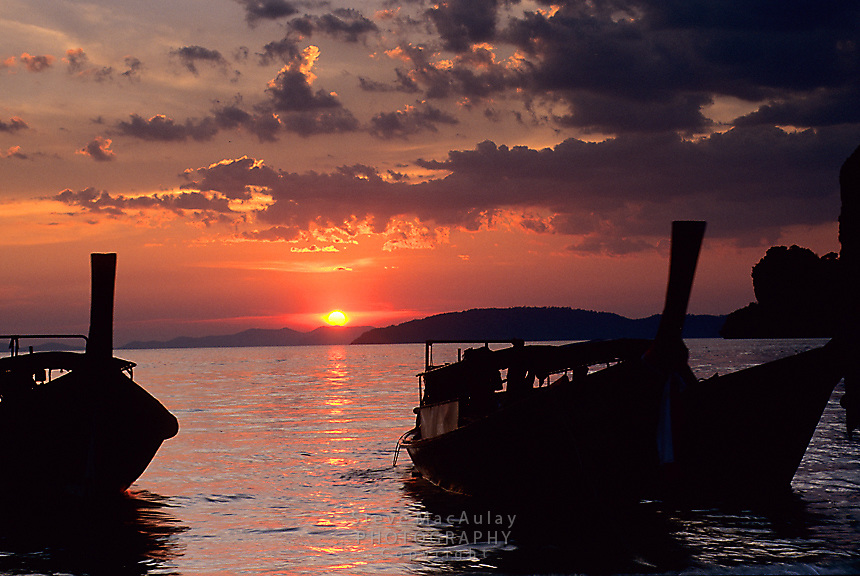 Colorful sunset behind traditional longtail boats pulled up on West Hat Railay Rei Lei Beach, Thailand