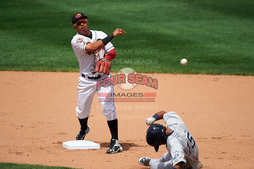 Rochester Red Wings shortstop Wilfredo Tovar (4) turns a double play as Yhoxian Medina (15) slides in during a game against the Columbus Clippers on June 16, 2016 at Frontier Field in Rochester, New York.  Rochester defeated Columbus 6-2.  (Mike Janes/Four Seam Images)