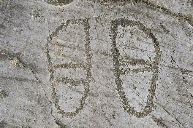 Petroglyph, rock carving, of two feet outlines. Carved by the ancient Camunni people in the iron age between 1000-1600 BC. Rock no 24,  Foppi di Nadro, Riserva Naturale Incisioni Rupestri di Ceto, Cimbergo e Paspardo, Capo di Ponti, Valcamonica (Val Camonica), Lombardy plain, Italy