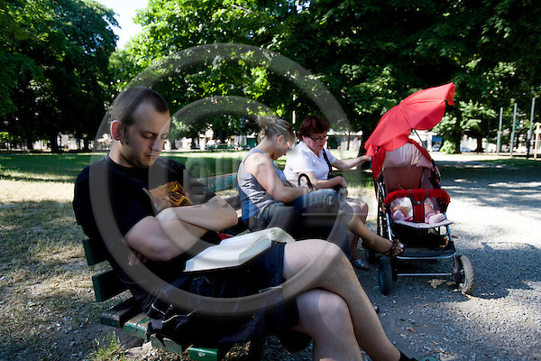 POZNAN - POLAND - 3 JUNE 2008 -- A young man enjoys a book on the bench in the city park. Next to him a young mother with her baby in a pram and the grandmother. Photo: Erik Luntang/EUP-IMAGES