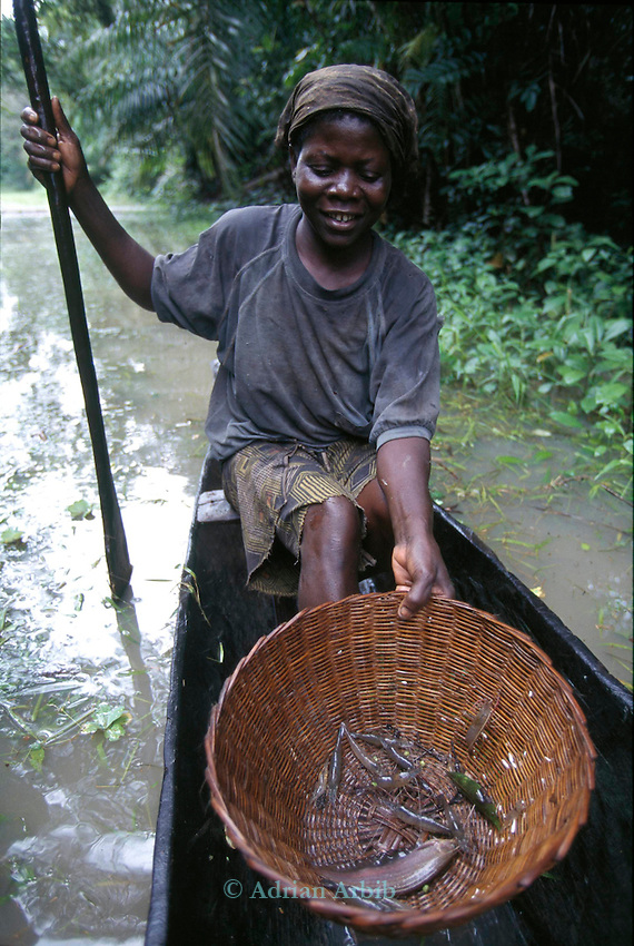An Ijaw woman  and her fish catch from a communal forest around her village in the Delta region of Nigeria.  The fish catch has dropped dramatically as  a result of oil spillage from  a nearby Shell Oil extraction  pipe