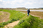 Woman walking on flood defence embankment wall River Alde, Aldeburgh, Suffolk, England