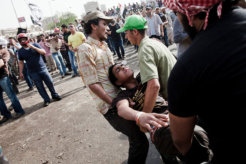 An injured Egyptian demonstrator is helped away from violent clashes between protesters and Military Police in front of the Egyptian Ministry of Defense in central Cairo's suburb of Abbaseya, March 4, 2012. Protesters marched on the MOD to demonstrate against over 20 deaths during a sit-in protest two days before. Photo: Ed Giles.