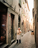 ITALY, Orvieto, Umbria, chocolatier Moreno Gambelli  standing on alley amid buildings