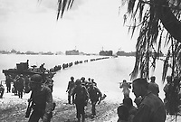 Army reinforcements disembarking from LST's form a graceful curve as they proceed across coral reef toward the beach.  Saipan, ca.  June/July 1944.  Laudansky.  (Army)<br /> Exact Date Shot Unknown<br /> NARA FILE #:  111-SC-191475<br /> WAR & CONFLICT BOOK #:  1168