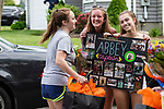 WATERTOWN, CT. 04 June 2020-060420BS234 - Watertown Girls Tennis team players Morgan Bennett, center, and Emma Kite, right, give quad captain and teammate Abbey Holly a photo board collage as they, coaches, parents and other players drive by and honor the Watertown Girls Tennis team seniors in a car parade on Thursday. Bill Shettle Republican-American