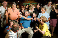 Owners of The Loop Taste of Chicago, Mark Rusin (cq, in blue) and his wife Marcie Rusin (cq, in middle pointing) are surrounded by friends and customers in their restaurant in Tucson, Arizona, Thursday, August 6, 2009. Rusin was denied a small business emergency loan designed to help people as part of the stimulus package...PHOTOS/ MATT NAGER