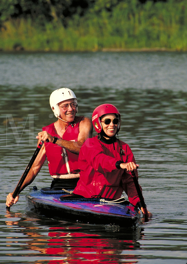 Senior couple kayaking in Shawnee Mission Park Lake, Kansas with safety gear, smiling, couples, kayaks, adventure MRS#602. Restrictions may be waived--contact photographer. Overland Park Kansas.