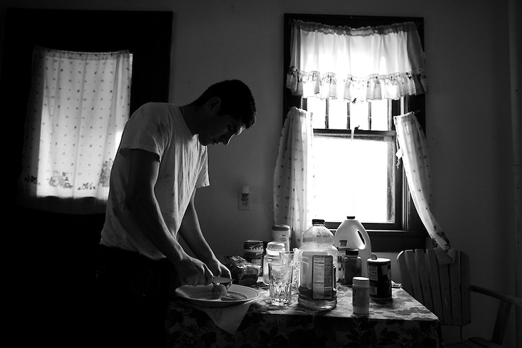 Jorge Moreno Gomez fixes a sandwich at his farmhouse near the Weiss Dairy Farm in Swan Lake, NY. Gomez has worked at the farm for six months, and was given room and board at an old farmhouse by the owner.