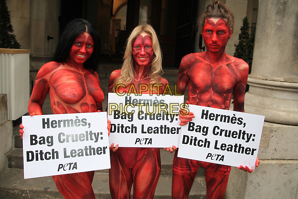 """Skinned People Protest at Hermes Leather Exhibition.Painted to resemble bloodied and skinned people, three models representing PETA will converge outside the opening of the """"Hermès Leather Forever"""" exhibition at the Royal Academy of Arts at 6 Burlington Gardens on Tuesday. They will hold signs reading, """"Hermès, Bag Cruelty: Ditch Leather"""", while other PETA members hand out leaflets to passers-by and event attendees. In addition to causing a life of suffering and a terrifying death for cows and other animals killed for their skin, the leather industry is toxic to the environment and a threat to human health. Unlike more progressive companies, Hermès also uses fur. L- R Monica Harris, Katy Heffernan-Smith, Niki Verb.half length red paint naked nude poster signs.CAP/JEZ  .©Jez/Capital Pictures."""