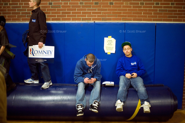 People watch Mitt Romney speak in the overflow area in a gymnasium at a Romney town hall campaign event at McKelvie Intermediate School in Bedford, New Hampshire, on Jan. 9, 2012.  Romney is seeking the 2012 Republican presidential nomination.
