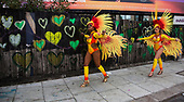 London, UK. 28 August 2017. Dancers from Paraiso School of Samba walk past green hearts remembering the Grenfell Tower disaster. Notting Hill Carnival celebrations and parade on Bank Holiday Monday. The festival attacts usually over 1 million visits and this year it remembers the victims of the Grenfell Tower fire.