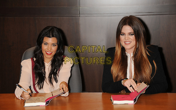 "Kourtney Kardashian, Khloe Kardashian Odom .at the ""Dollhouse"" book signing at Barnes & Noble bookstore at The Grove in Los Angeles, California, USA, November 18th, 2011.  .half length siblings sisters blouse white shirt beige black jacket sitting .CAP/ROT/TM.©TM/Roth Stock/Capital Pictures"