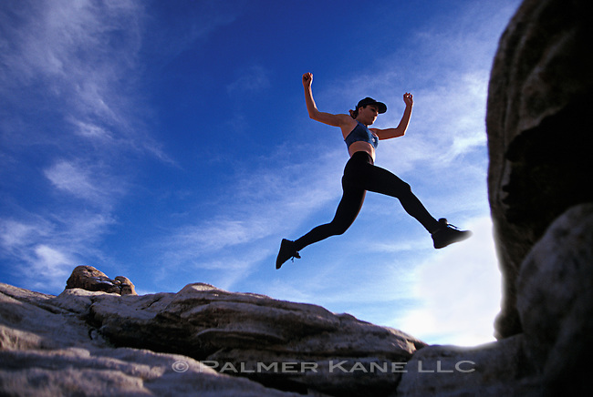 Female hiker jumping rocks in the BLM Red Rocks Canyon area near Las Vegas NV