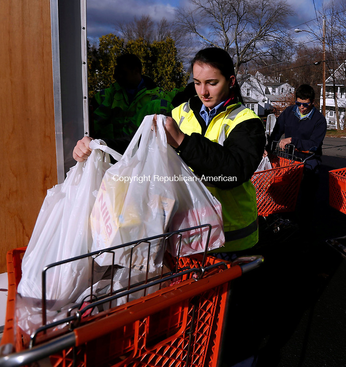 Plymouth, CT- 14 November 2015-111415CM01-  Antonela Velaj of Bristol loads donated food items onto a grocery cart at the Plymouth Community Food Pantry on Saturday.  The Plymouth Ambulance Corp held a food drive at the IGA Plaza.  The group collected over 600 pounds of food.   Christopher Massa Republican-American