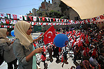 Palestinians hold Turkish flags during the opening ceremony of the Nablus Rashidiya girls school, in the West Bank city of Nablus, on May 7, 2015. The Nablus Resadiye girls school in Palestine was established in 1911. TIKA started restoration in 2014. The school has a 3,200 square meter area of usage, 12 classrooms, one playground, two computer labs and one kitchen. The school teaches 311 girls with 21 teachers and four administrative staff. Photo by Nedal Eshtayah
